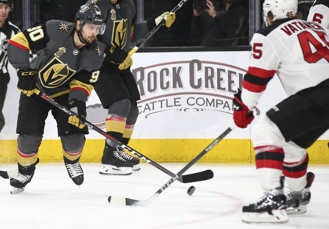 Golden Knights left wing Tomas Tatar (90) looks to get the puck past New Jersey Devils defenseman Sami Vatanen (45) during the first period of an NHL hockey game at T-Mobile Arena in Las Vegas on  ...