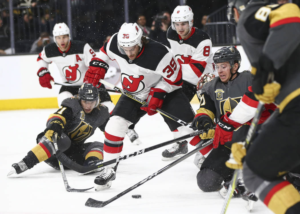 Golden Knights center Jonathan Marchessault, right, fights for the puck against New Jersey Devils left wing Brian Gibbons (39) as Golden Knights center William Karlsson, left, slips on the ice dur ...