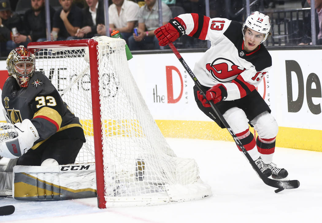 New Jersey Devils center Nico Hischier (13) skates around the goal as Golden Knights goaltender Maxime Lagace (33) defends  during the second period of an NHL hockey game at T-Mobile Arena in Las  ...