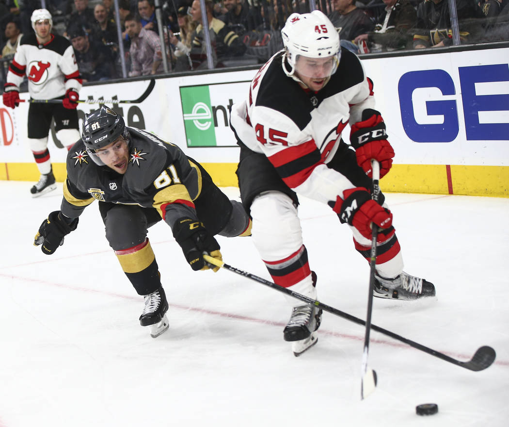 Golden Knights center Jonathan Marchessault (81) tries to get the puck from New Jersey Devils defenseman Sami Vatanen (45) during the third period of an NHL hockey game at T-Mobile Arena in Las Ve ...