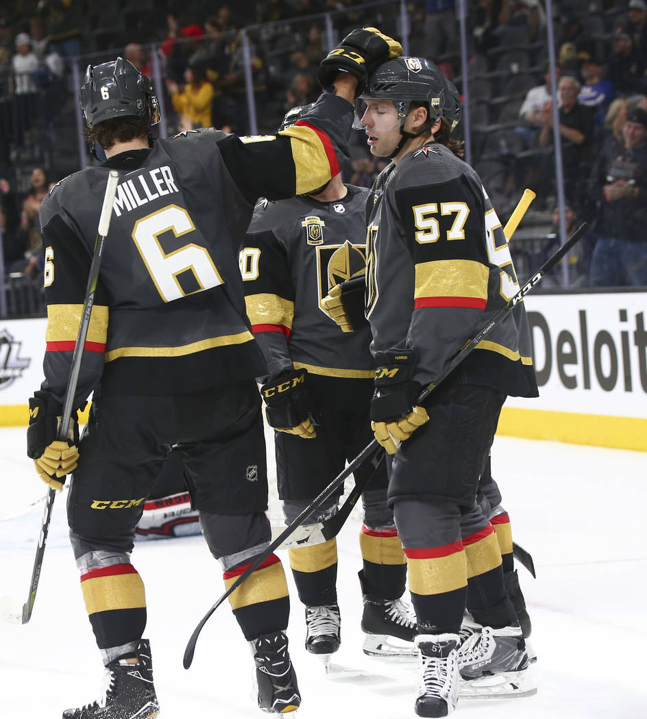 Golden Knights defenseman Colin Miller (6) and Golden Knights left wing David Perron (57) react after their team scored against the New Jersey Devils during the third period of an NHL hockey game  ...