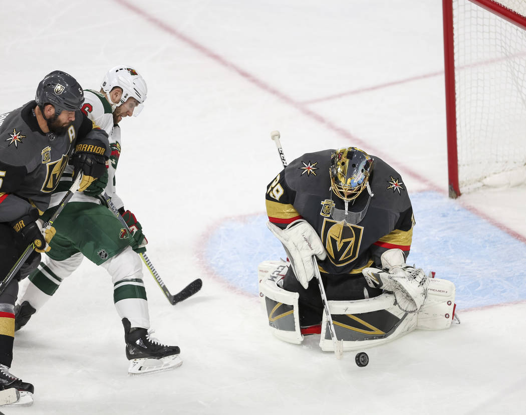 Vegas Golden Knights goaltender Marc-Andre Fleury (29) deflects the puck as Knights defenseman Deryk Engelland (5) and Minnesota Wild defenseman Ryan Murphy (6) chase for the rebound during the fi ...