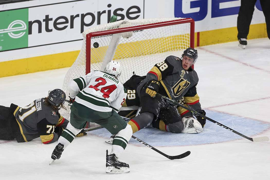Minnesota Wild defenseman Matt Dumba (24) shoots for a goal after defenseman Nate Schmidt (88) crashed into Knights goaltender Marc-Andre Fleury (29) during the second period of an NHL hockey game ...