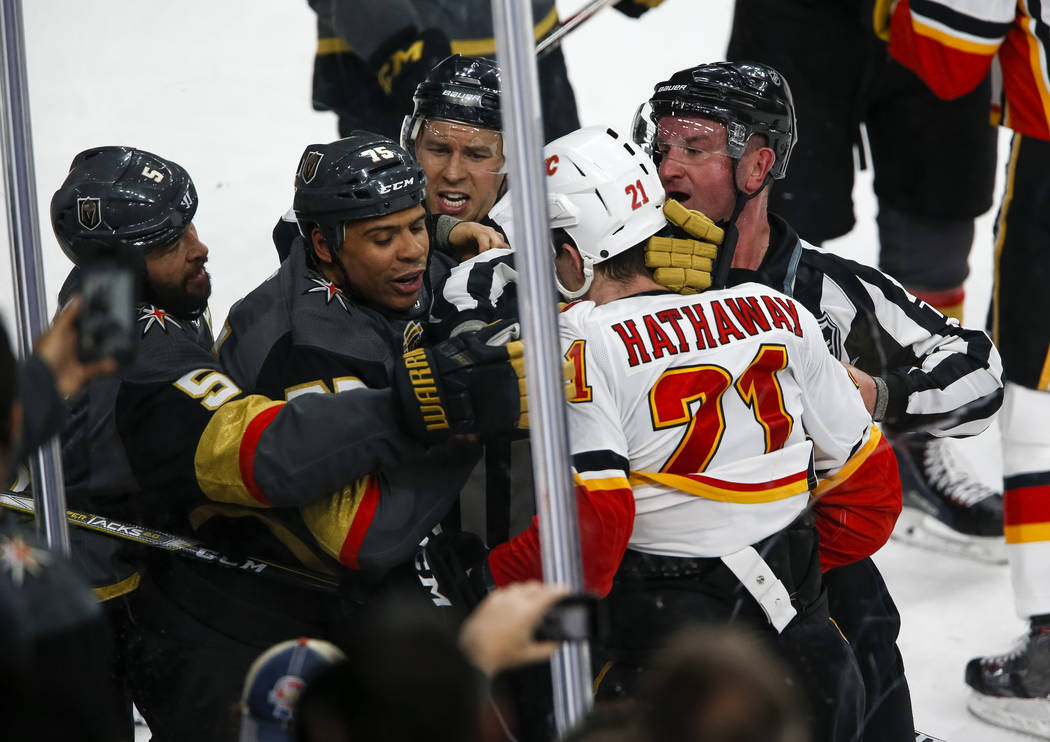 Vegas Golden Knights right wing Ryan Reaves, second left, fights with Calgary Flames right wing Garnet Hathaway (21) during the second period of an NHL hockey game between the Vegas Golden Knights ...