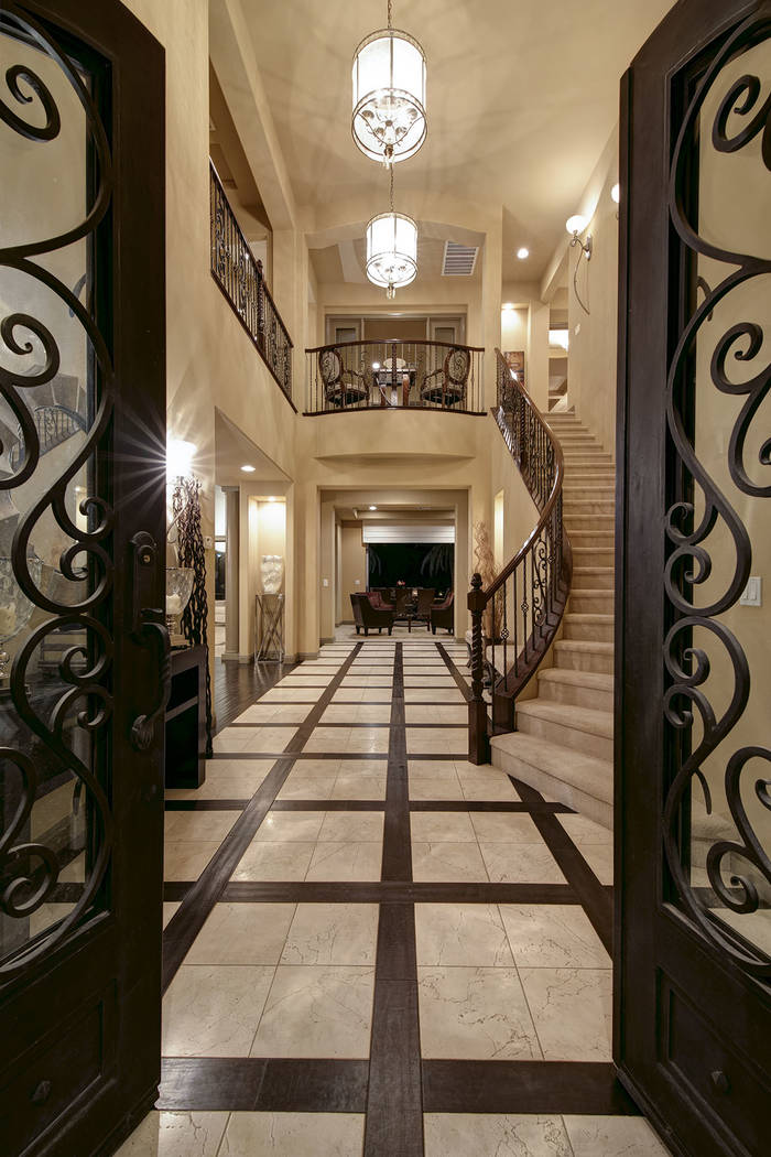 Its grand, wooden double-door entry opens into an expansive foyer with travertine flooring framed by wood accents. (Synergy/Sotheby's International Realty)