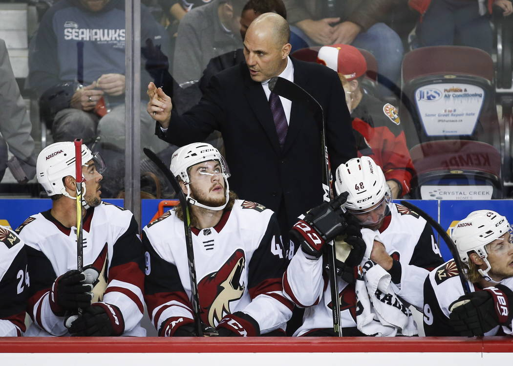 In this Sept. 22, 2017, file photo, Arizona Coyotes coach Rick Tocchet, center, gives instruction to players during the first period of a preseason NHL hockey game against the Calgary Flames in Ca ...