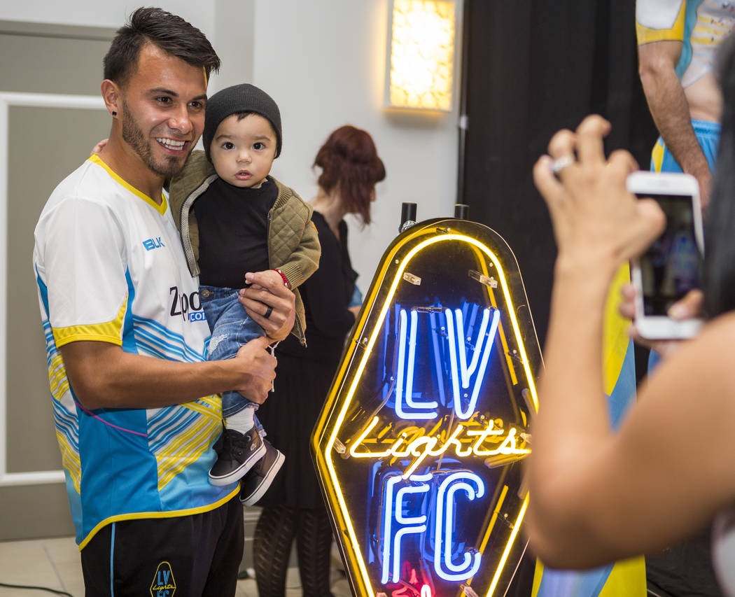 Las Vegas Lights midfielder Carlos Alvarez has his photo taken with his son Romeo, 1, by his wife Renae Cuellar, a soccer player with the Mexican national team, at the Las Vegas Lights FC season k ...