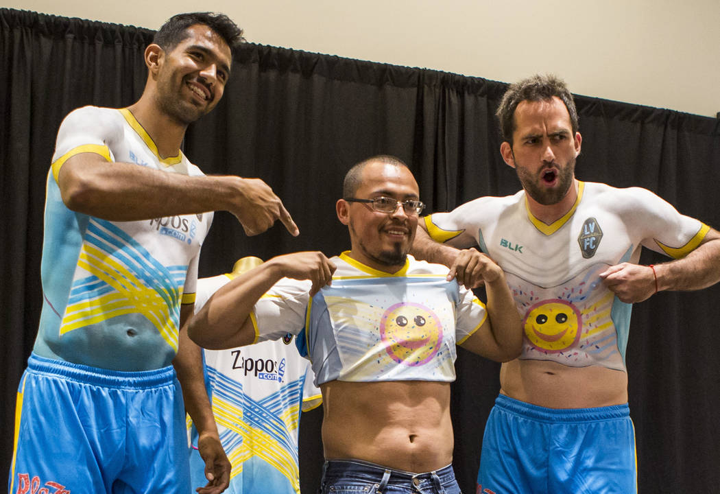 Miguel Garduno, left, and Juan Carlos Garcia, right, pose for a photo with a fan at the Las Vegas Lights FC season kickoff party at the Plaza in downtown Las Vegas on Wednesday, March 14, 2018.  P ...