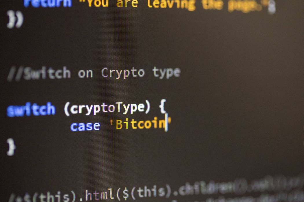 A developer types up a bitcoin/cryptocurrency programming code in Las Vegas Monday, March 12, 2018. (Richard Brian/Las Vegas Review-Journal via AP)
