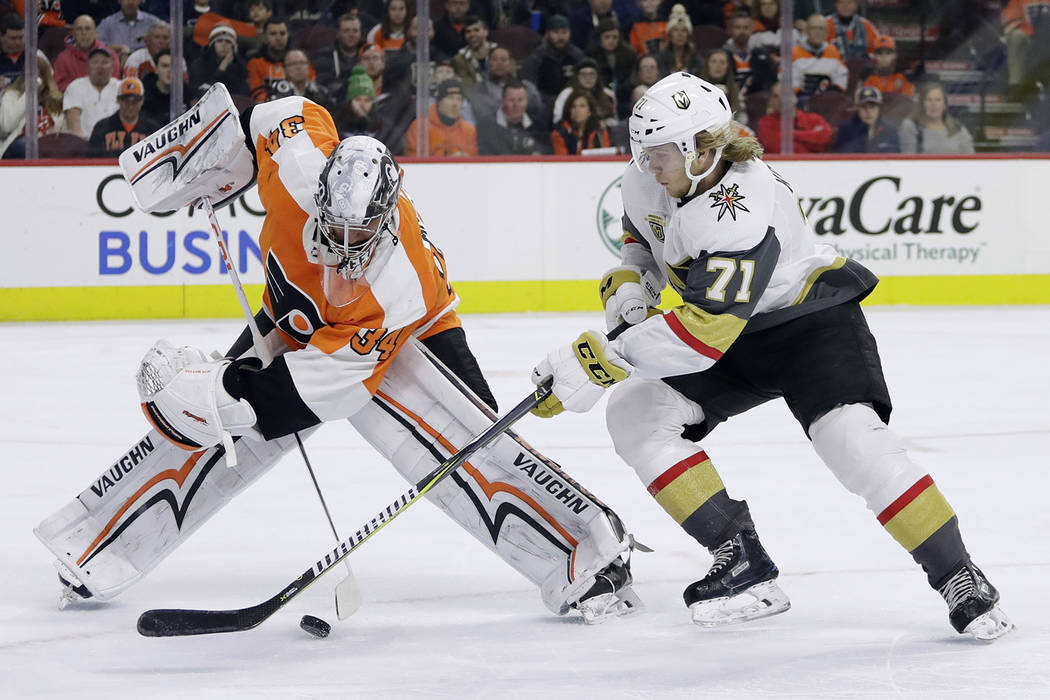 Philadelphia Flyers' Petr Mrazek, left, and Vegas Golden Knights' William Karlsson battle for the puck during the first period of an NHL hockey game, Monday, March 12, 2018, in Philadelphia. (AP P ...