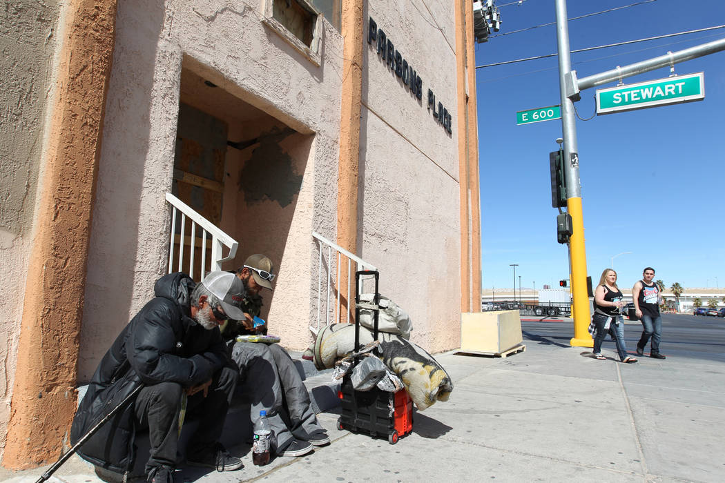 Larry G. Wampler Jr. left, and Chase Michael Hoover, who said they are homeless, eat meals that were dropped off by a motorist in front of a vacant apartment complex on North 7th Street at Stewart ...