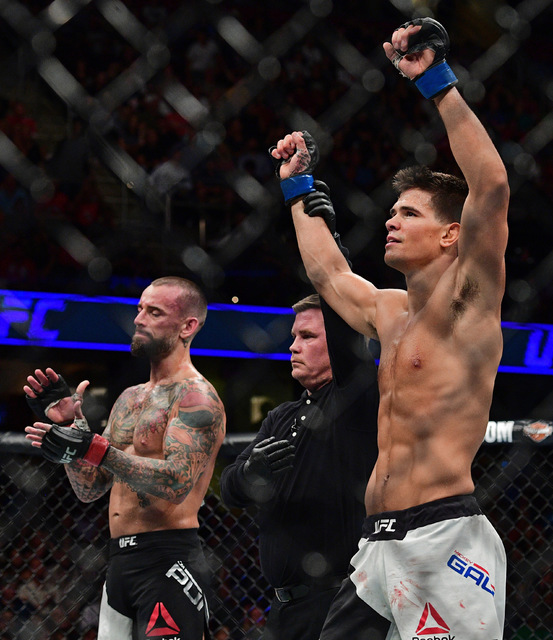 Mickey Gall has his arm raised by the referee after defeating CM Punk during a welterweight bout at UFC 203 on Saturday, Sept. 10, 2016, in Cleveland. (AP Photo/David Dermer)
