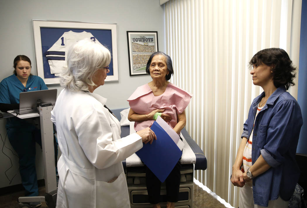 Dr. Mary Ann Allison, an oncologist with the Comprehensive Cancer Centers of Nevada, talks to her patient Sonia Roldan, 75, center, at the centers as Roldan's daughter Ana Quimpo, right, also Dr.  ...