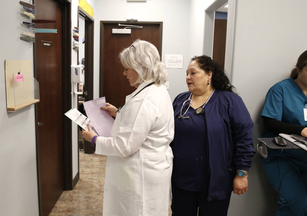 Dr. Mary Ann Allison, an oncologist with the Comprehensive Cancer Centers of Nevada, left, glances through the records before seeing a patient, as Brenda Fonseca, a medical assistant, looks on at  ...