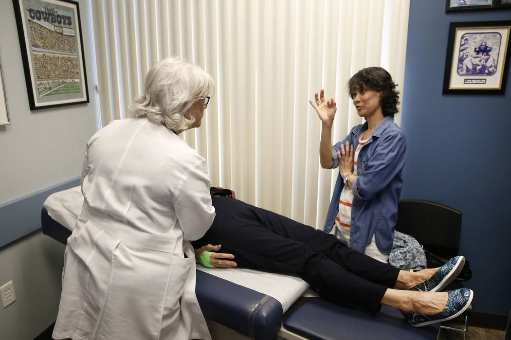 Dr. Mary Ann Allison, an oncologist with the Comprehensive Cancer Centers of Nevada, listens to Ana Quimpo at the centers while examining Quimpo's mother, Sonia Roldan, 75, on Thursday, March 15,  ...