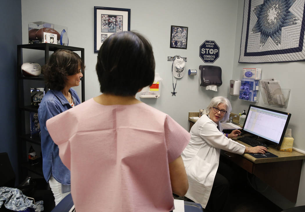 Dr. Mary Ann Allison, an oncologist with the Comprehensive Cancer Centers of Nevada, right, discusses about lab test results at the centers with her patient, Sonia Roldan, center, as Roldan's daug ...