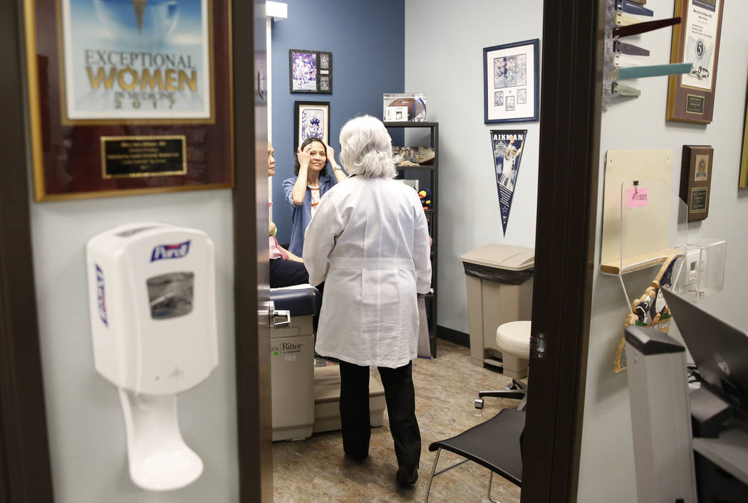 Dr. Mary Ann Allison, an oncologist with the Comprehensive Cancer Centers of Nevada, enters an exam room at the centers to see her patient Sonia Roldan, 75, left, as Roldan's daughter Ana Quimpo,  ...