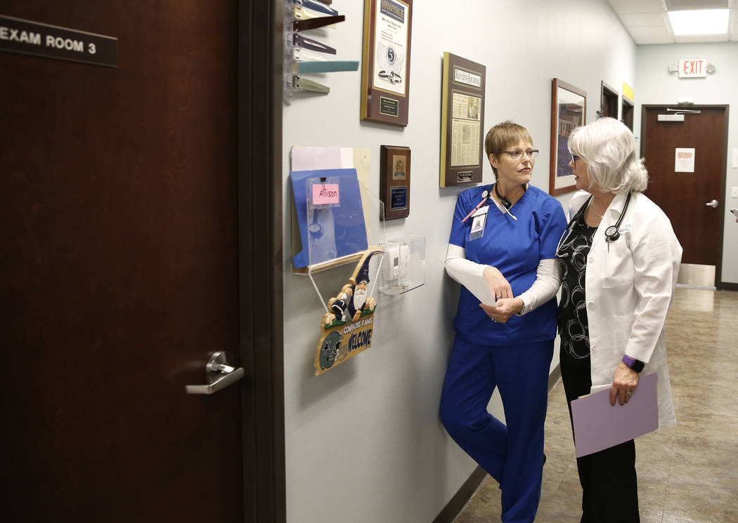 Dr. Mary Ann Allison, an oncologist with the Comprehensive Cancer Centers of Nevada, right, discusses with Kristin Waltz, a registered nurse, as she prepares to see her patient at the centers on T ...