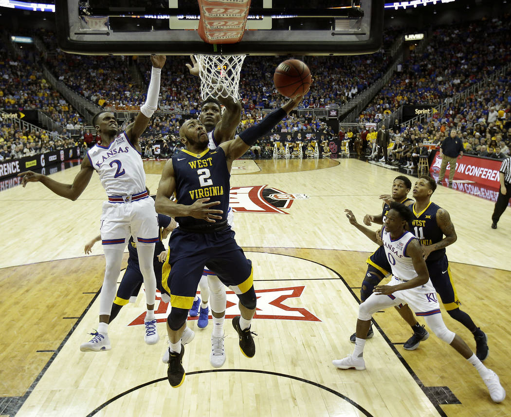 West Virginia's Jevon Carter puts up a shot during the first half of the NCAA college basketball championship game against Kansas in the Big 12 men's tournament Saturday, March 10, 2018, in Kansas ...