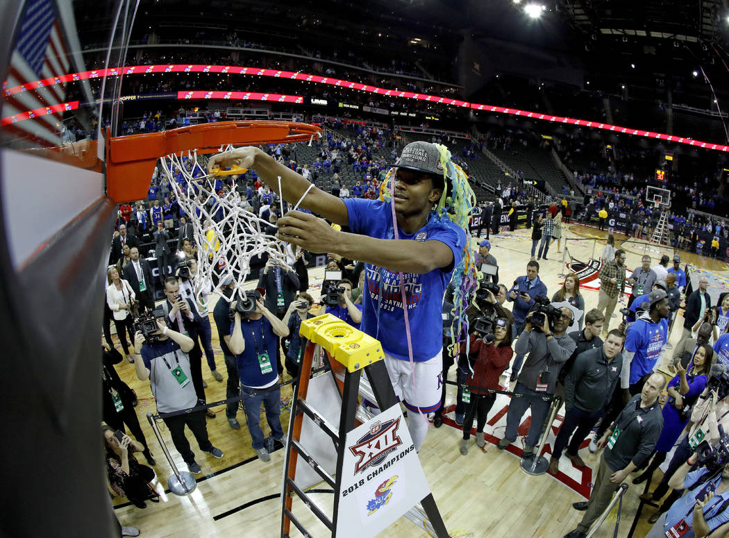 Kansas' Devonte' Graham cuts the net after winning the NCAA college basketball championship game against West Virginia in the Big 12 men's tournament Saturday, March 10, 2018, in Kansas City, Mo.  ...