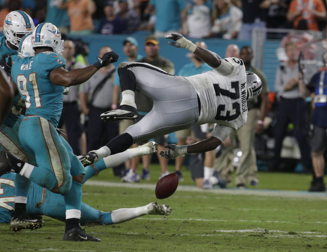 Oakland Raiders offensive tackle Marshall Newhouse (73) trips over Miami Dolphins middle linebacker Kiko Alonso (47) and fumbles the ball during the second half of an NFL football game, Sunday, No ...