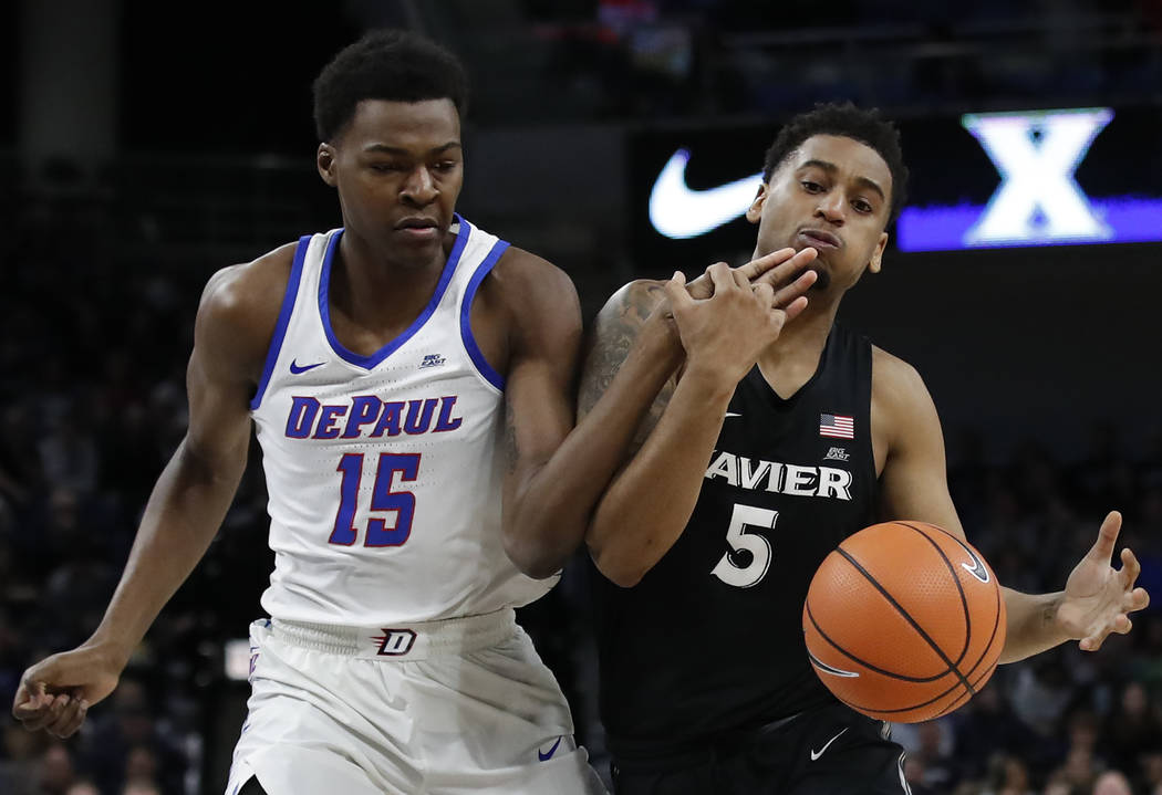 Xavier guard Trevon Bluiett (5) is fouled by DePaul forward Paul Reed (15) during the first half of an NCAA college basketball game Saturday, March 3, 2018, in Chicago, Ill. (AP Photo/Jim Young)