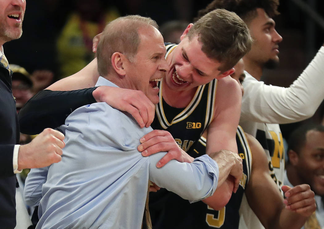 Michigan head coach John Beilein, left, celebrates with Michigan forward Moritz Wagner (13) after Michigan defeated Purdue 75-66 to win the NCAA Big Ten Conference tournament championship college  ...