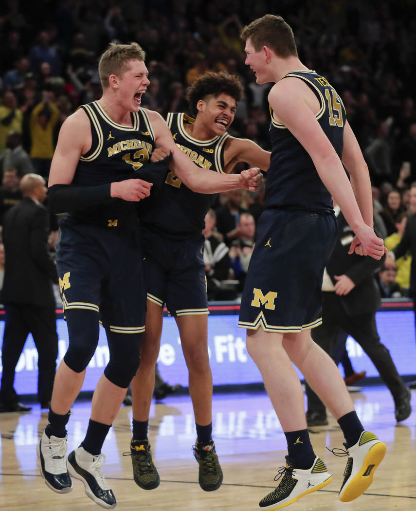 From left, Michigan forward Moritz Wagner, guard Jordan Poole (2) and center Jon Teske (15) celebrate after Michigan beat Purdue of the NCAA Big Ten Conference tournament championship college bask ...