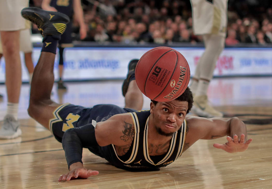 Michigan guard Zavier Simpson (3) dives after a loose ball during the second half of the NCAA Big Ten Conference tournament championship college basketball game, Sunday, March 4, 2018, in New York ...