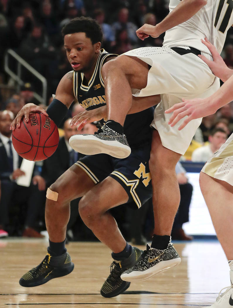 Michigan guard Zavier Simpson (3) is fouled as he drives to the basket against Purdue during the second half of the NCAA Big Ten Conference tournament championship college basketball game, Sunday, ...