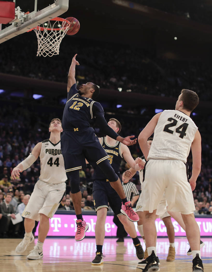 Michigan guard Muhammad-Ali Abdur-Rahkman (12) puts up a shot against Purdue during the second half of the NCAA Big Ten Conference tournament championship college basketball game, Sunday, March 4, ...