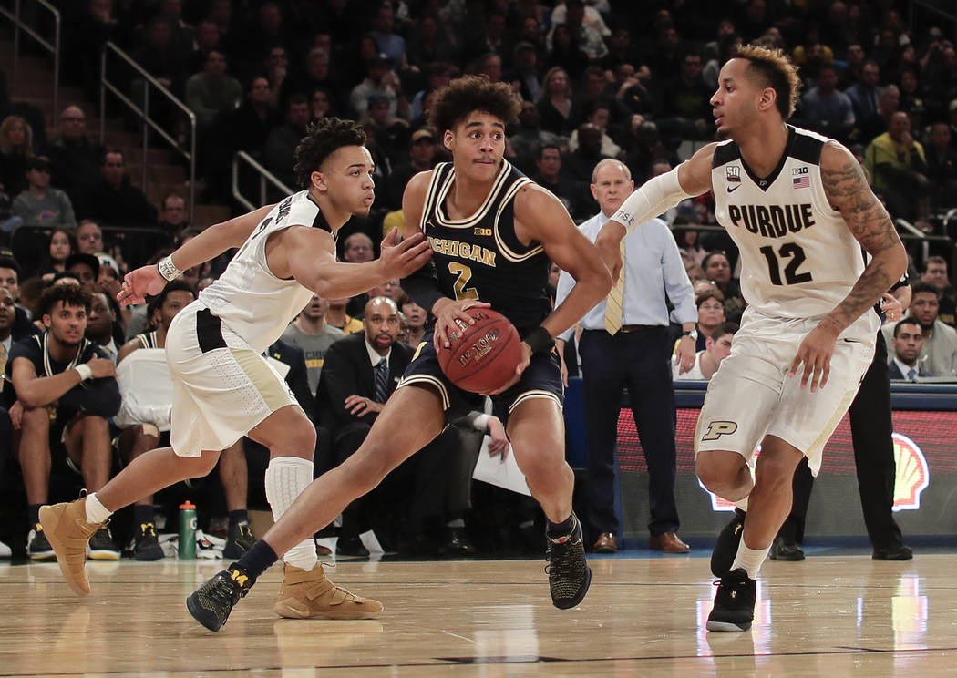 Michigan guard Jordan Poole (2) drives against Purdue guard Carsen Edwards (3) and forward Vincent Edwards (12) during the second half of the NCAA Big Ten Conference tournament championship colleg ...