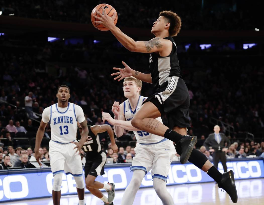 Providence's Makai Ashton-Langford (1) drives past Xavier's J.P. Macura (55) and Naji Marshall (13) during the second half of an NCAA college basketball game in the Big East men's tournament semif ...