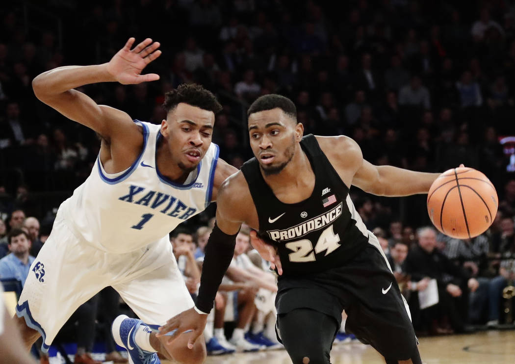 Providence's Kyron Cartwright (24) drives past Xavier's Paul Scruggs (1) during the second half of an NCAA college basketball game in the Big East men's tournament semifinals Friday, March 9, 2018 ...