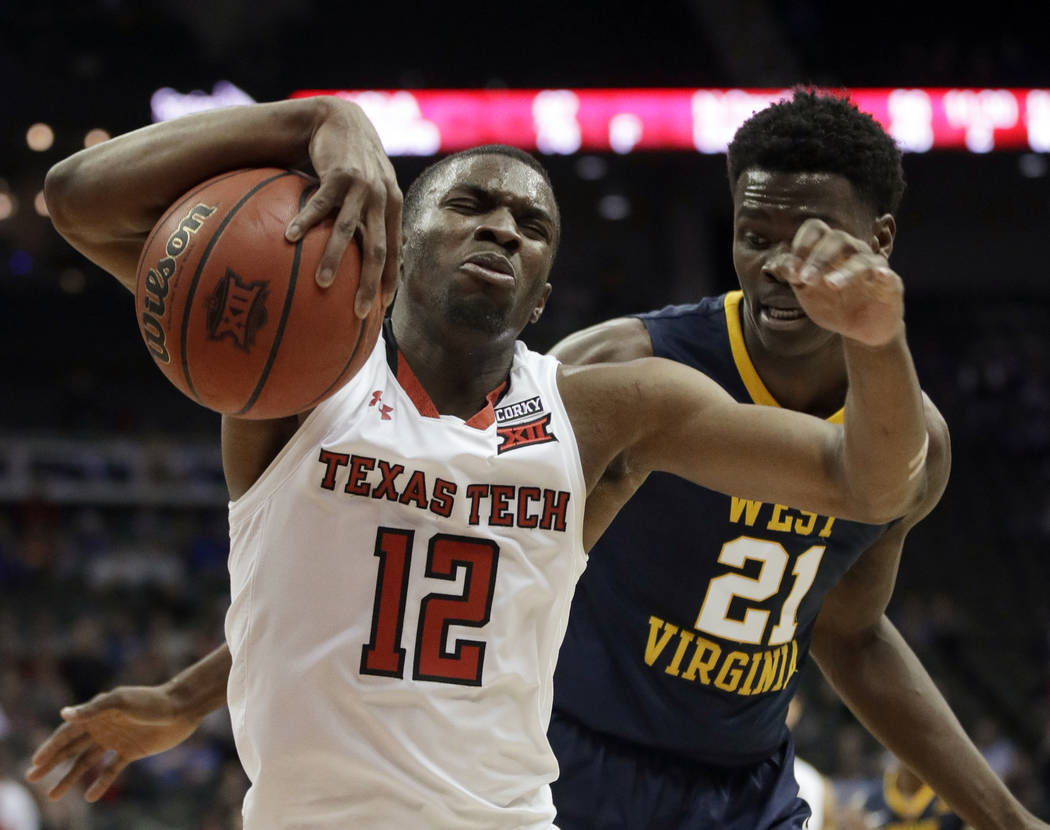 Texas Tech guard Keenan Evans (12) is fouled by West Virginia forward Wesley Harris (21) during the second half of an NCAA college basketball game in semifinals of the Big 12 men's tournament in K ...