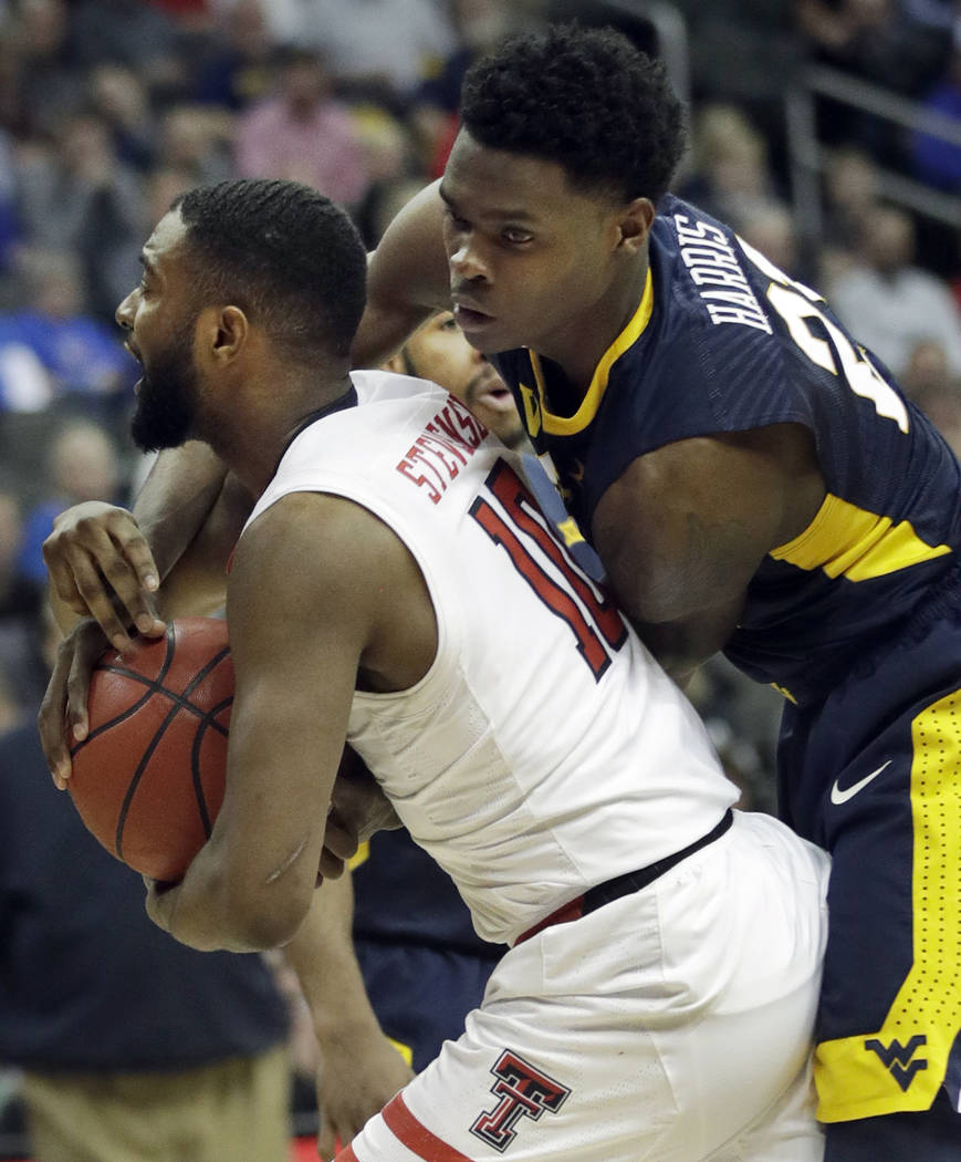 West Virginia forward Wesley Harris (21) ties up Texas Tech guard Niem Stevenson (10) during the second half of an NCAA college basketball game in semifinals of the Big 12 men's tournament in Kans ...