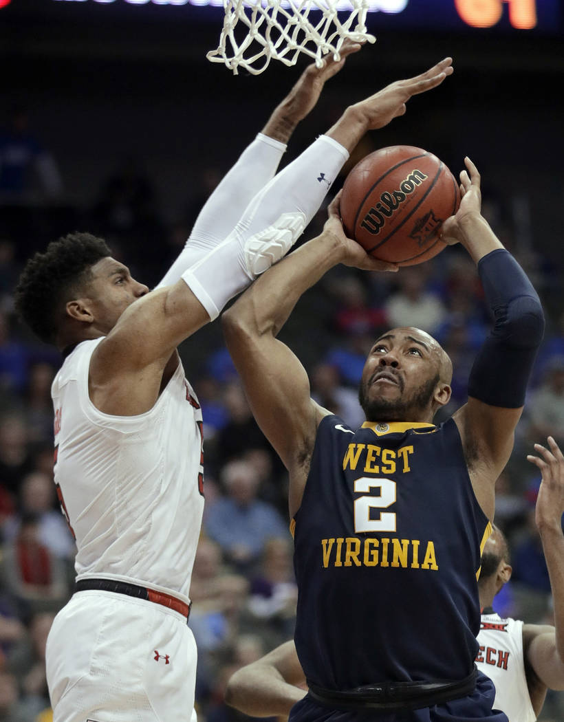 West Virginia guard Jevon Carter (2) shoots as Texas Tech guard Justin Gray defends during the second half of an NCAA college basketball game in semifinals of the Big 12 men's tournament in Kansas ...