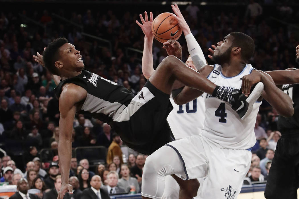 Providence's Rodney Bullock (5) falls as Villanova's Eric Paschall (4) blocks his shot during the second half of an NCAA college basketball game in the Big East men's tournament final Saturday, Ma ...