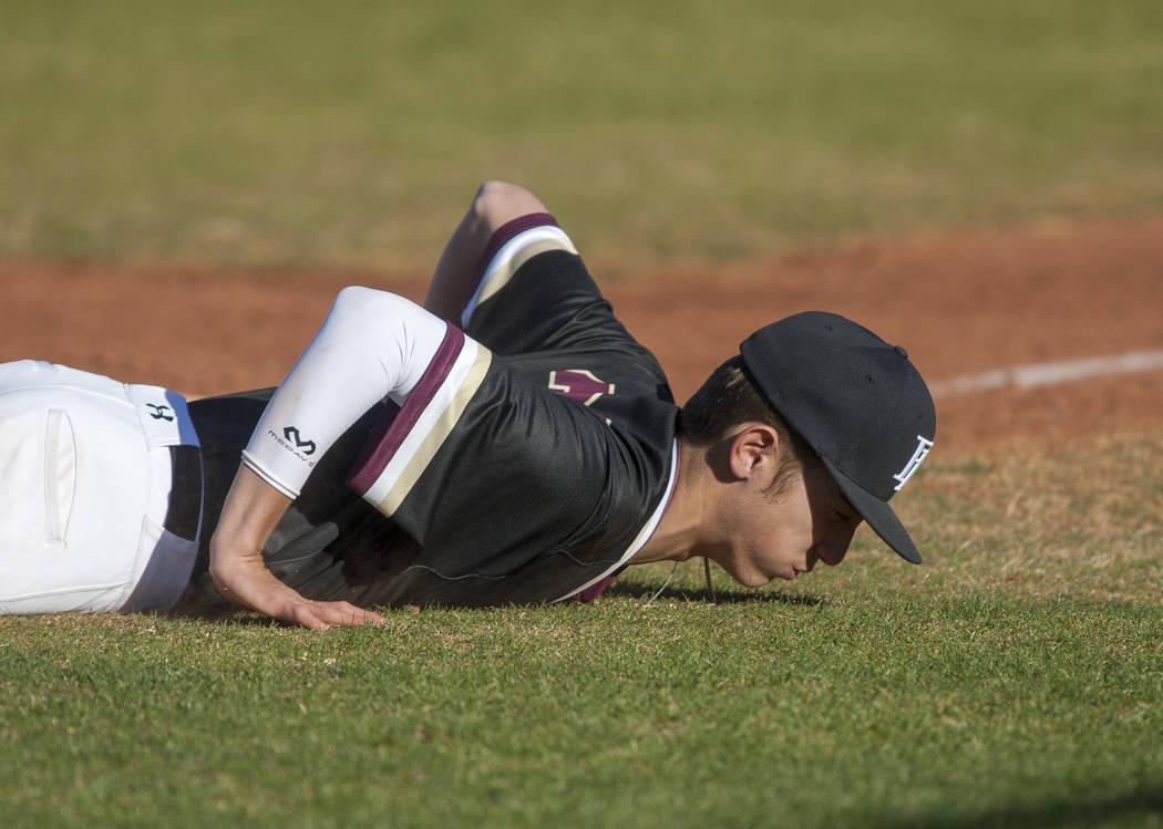 Faith Lutheran infielder Vance Serrano on the ground after failing to catch a line drive during the top of the fifth inning while playing against Centennial at Faith Lutheran High School in Las Ve ...