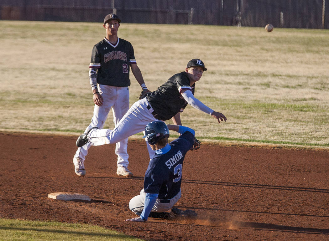 Faith Lutheran infielder Lucas Dockery tags out Centennial pitcher Zack Simon at second base and throws to first for a double play while Faith Lutheran infielder Michael Rice stands in the backgro ...