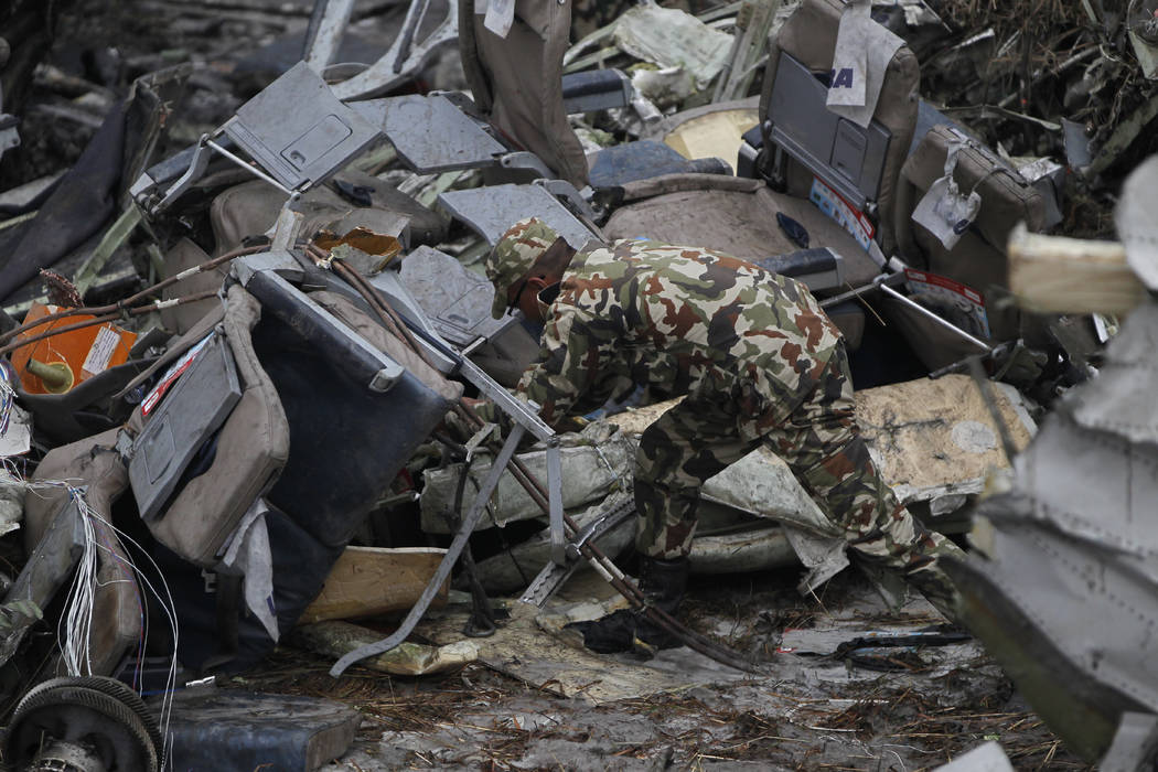 A Nepalese rescuer searches amid the debris after a passenger plane from Bangladesh crashed at the airport in Kathmandu Nepal Monday