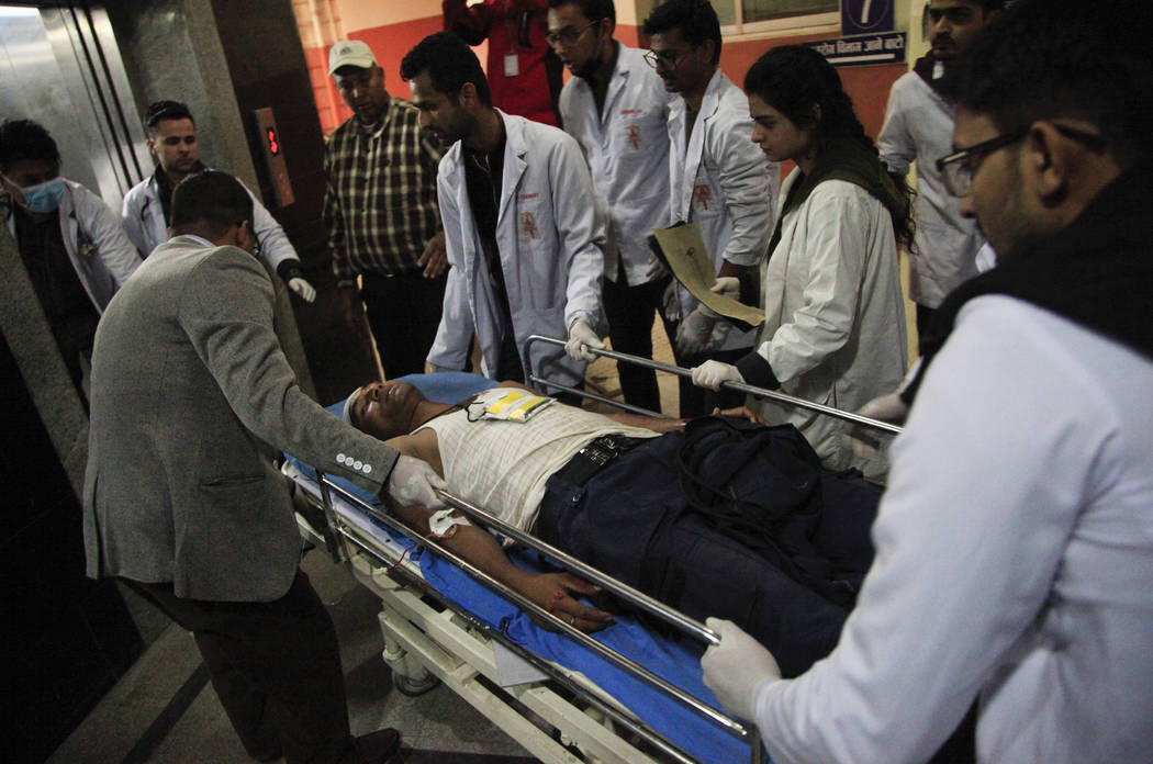 Nepalese doctors attend to an unidentified man injured in a plane crash in Kathmandu, Nepal, Monday, March 12, 2018. A plane carrying dozens of people from Bangladesh swerved erratically and flew  ...