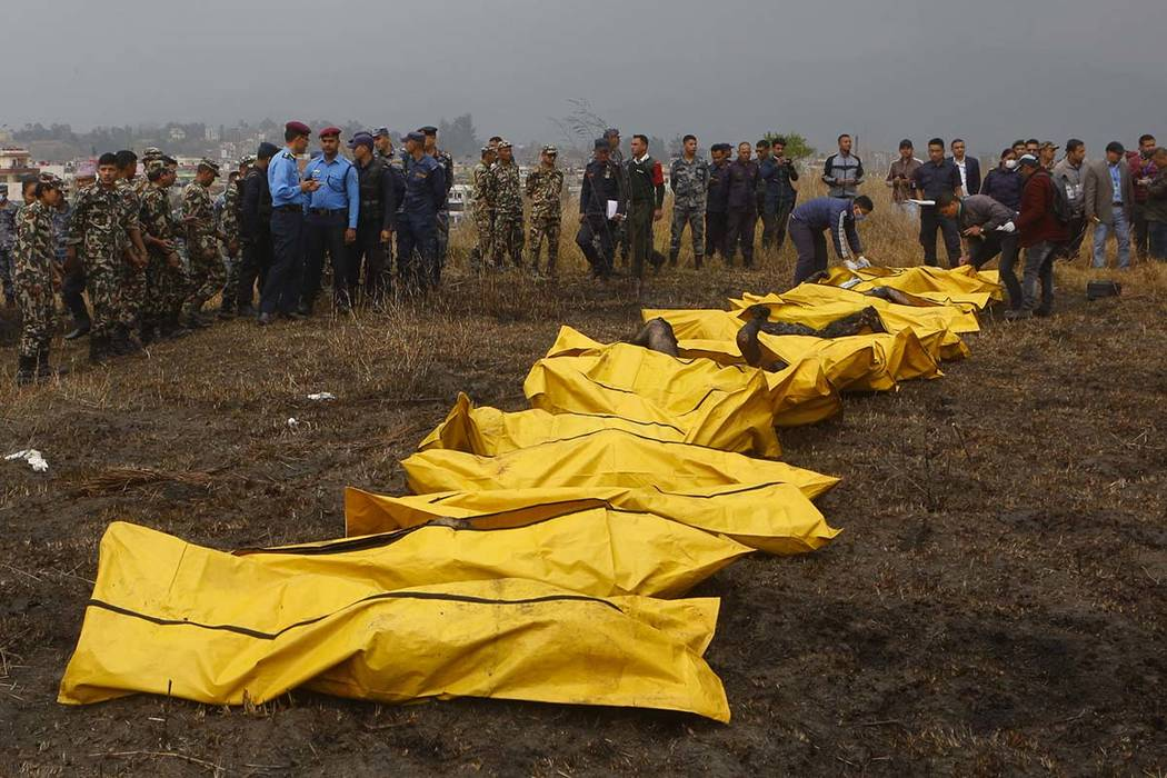 Nepalese rescuers attend to bodies of victims after a passenger plane from Bangladesh crashed at the airport in Kathmandu, Nepal, Monday, March 12, 2018. The passenger plane carrying 71 people fro ...