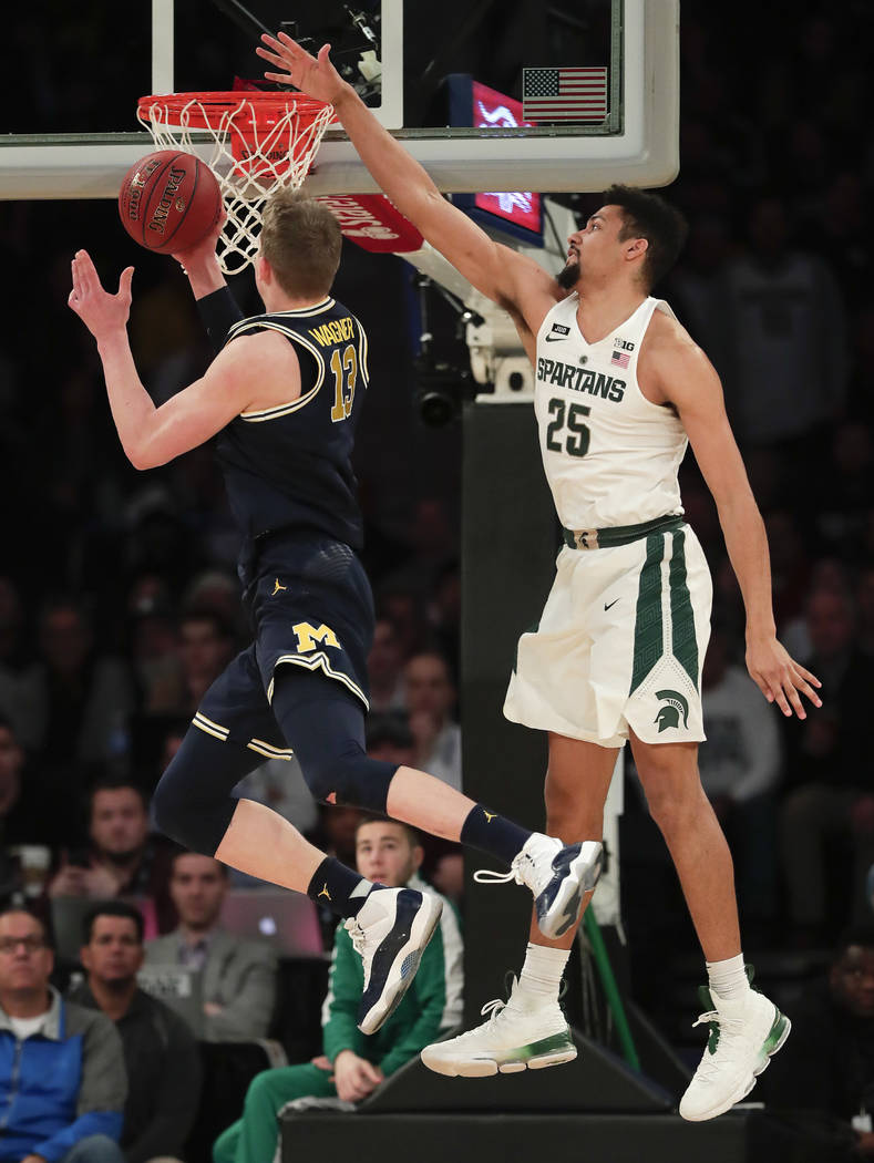 Michigan forward Moritz Wagner (13) puts up a shot against Michigan State forward Kenny Goins (25) during the first half of an NCAA Big Ten Conference tournament semifinal college basketball game, ...
