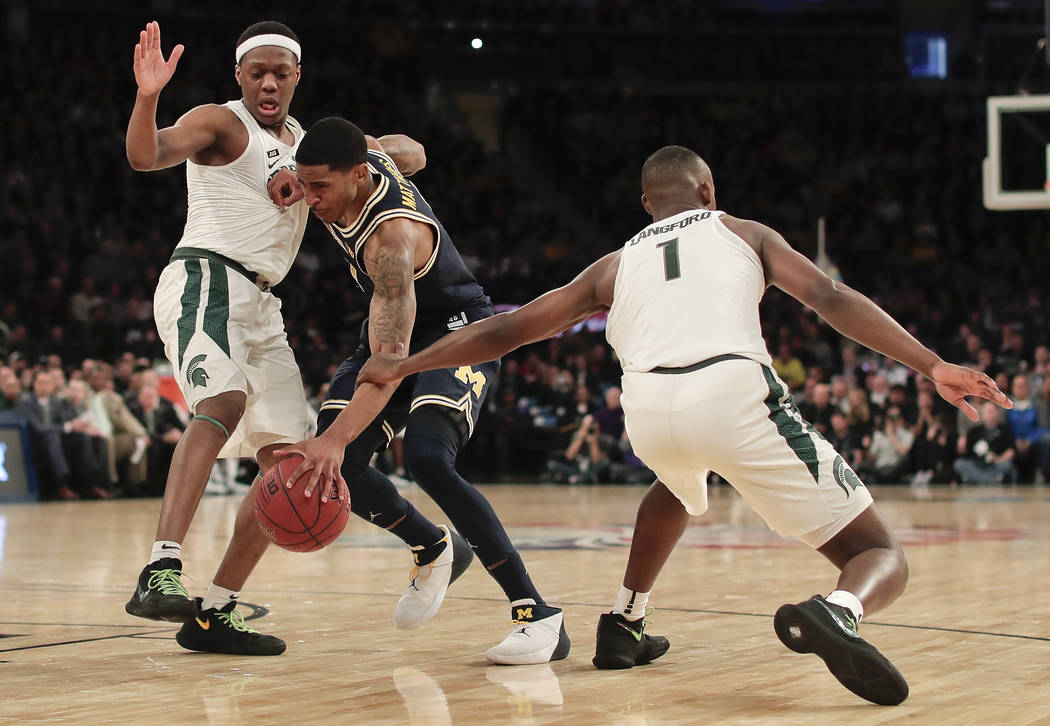 Michigan guard Charles Matthews (1) is fouled as he drives between Michigan State guard Cassius Winston, left, and guard Joshua Langford (1) during the second half of an NCAA Big Ten Conference to ...