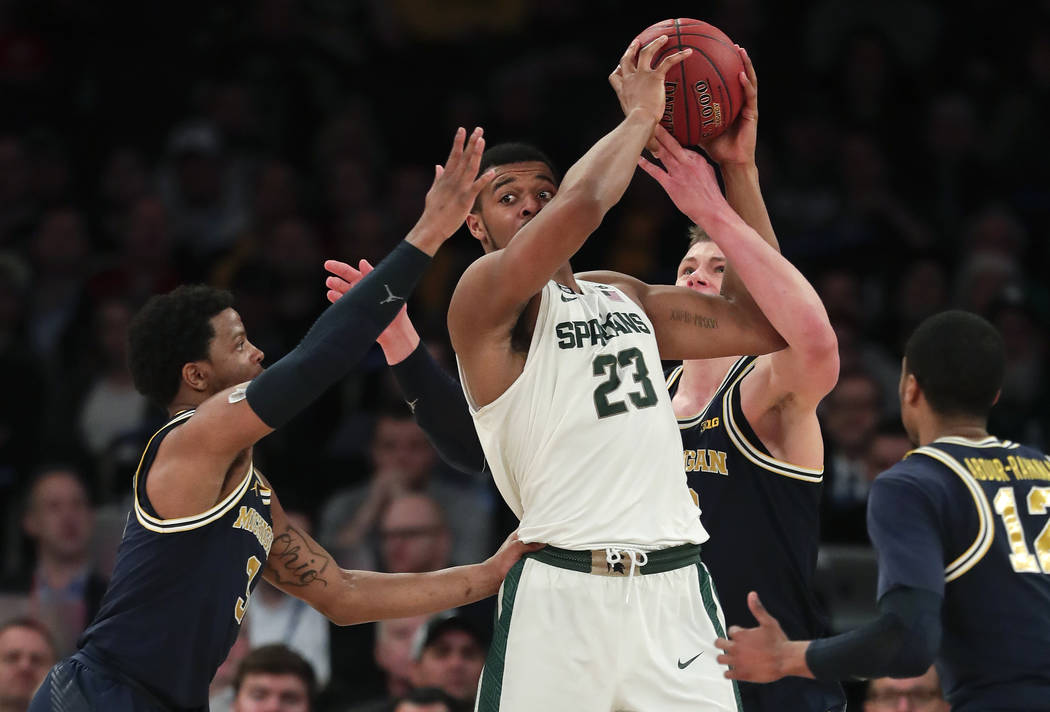 Michigan State forward Xavier Tillman (23) is double teamed by Michigan guard Zavier Simpson (3) and forward Moritz Wagner (13) during the second half of an NCAA Big Ten Conference tournament semi ...