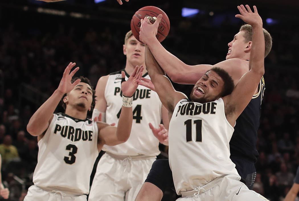 Michigan forward Moritz Wagner, right, pulls down a rebound against Purdue guard P.J. Thompson (11) during the second half of the NCAA Big Ten Conference tournament championship college basketball ...
