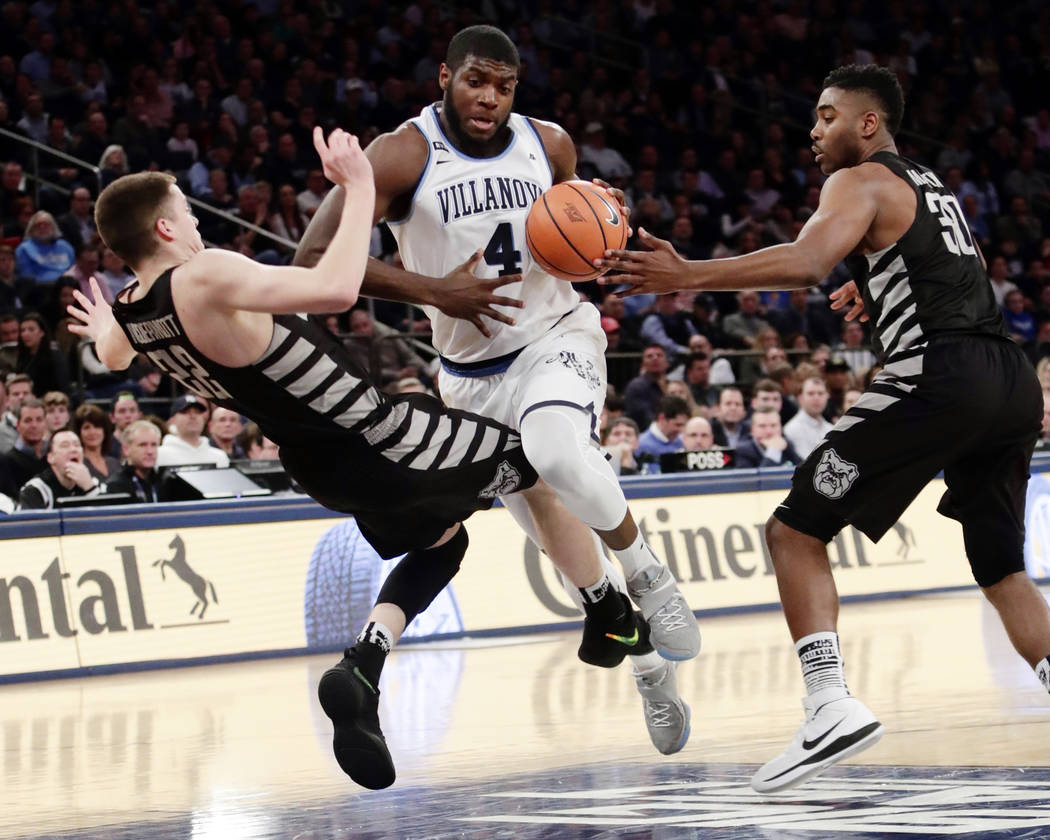 Villanova's Eric Paschall (4) drives past Sean McDermott (22) and Kelan Martin (30) during the first half of an NCAA college basketball game in the Big East men's tournament semifinals Friday, Mar ...