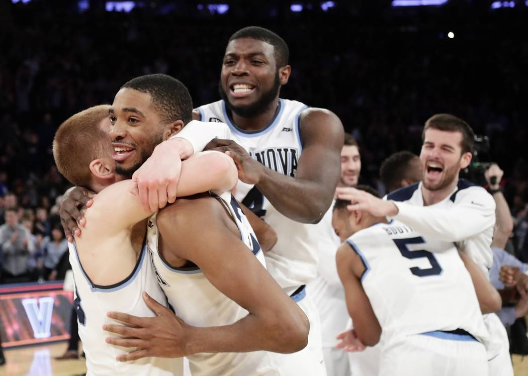 Villanova's Donte DiVincenzo, left, Mikal Bridges, Eric Paschall (4) and teammates, rear, celebrate after an NCAA college basketball game against Providence in the Big East men's tournament final  ...