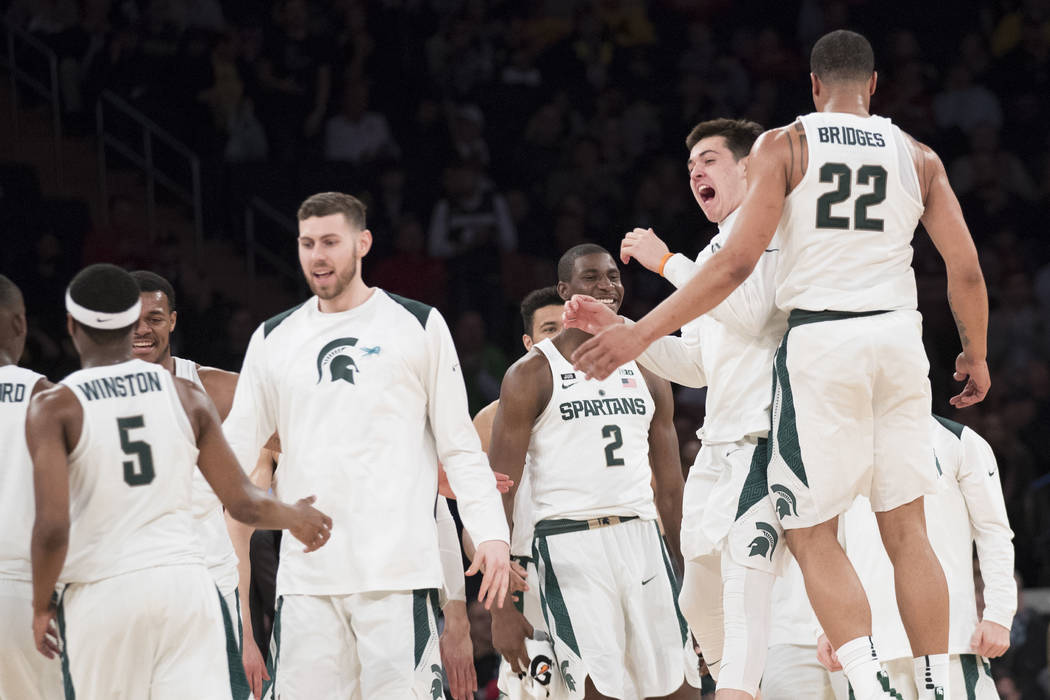 Michigan State guard Miles Bridges (22) celebrates with his teammates while coming into the bench during a time out in the second half of an NCAA college basketball game against Wisconsin in the q ...